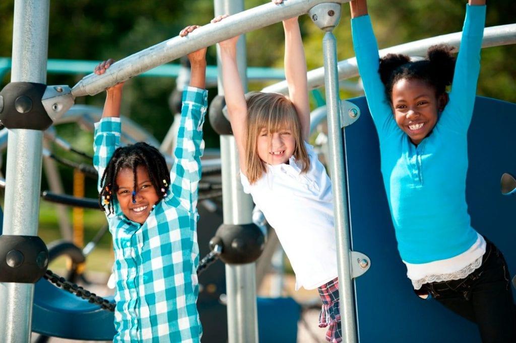 children hanging from monkey bars