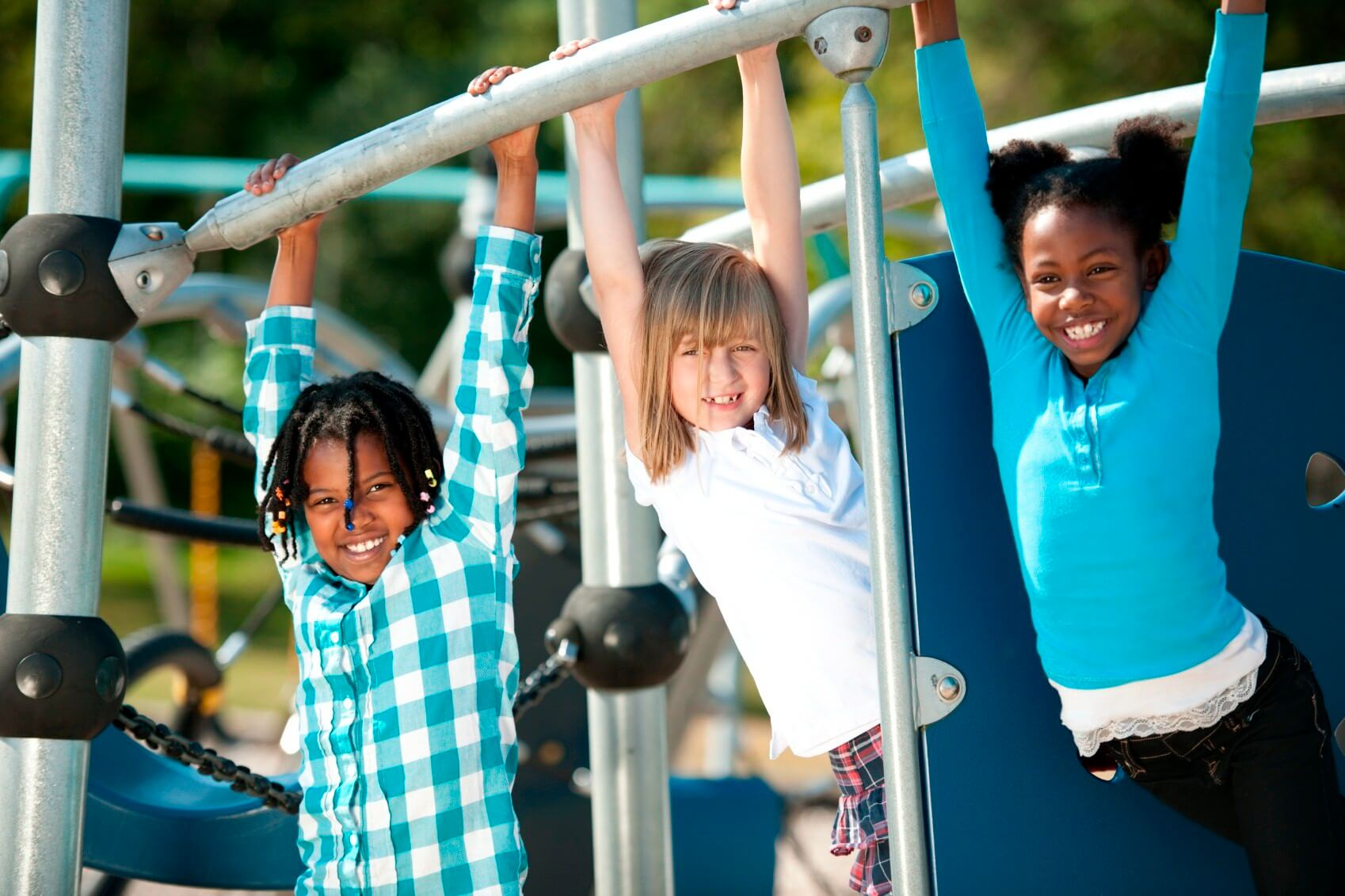 children hanging from monkey bars