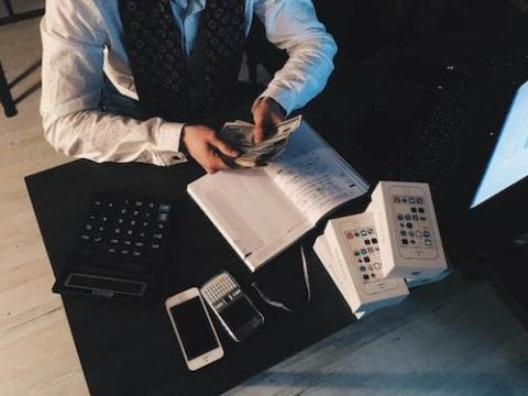 man sitting at desk counting money